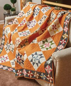 Liz Porter and some of her friends began a fabric exchange by pulling dark and light prints for Pinwheel quilt blocks. Liz stitched one at the center of each Martha Washington's Star block in this quilt and used the rest for the border.