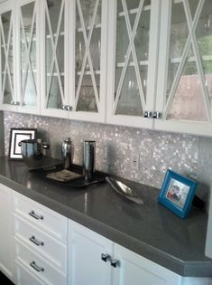 Glass front white cabinets, solid grey counter and White mother of pearl backsplash: Found at https://www.subwaytileoutlet.com/