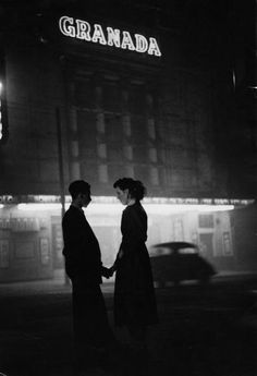 a young couple hold hands outside the granada cinema, london, england, april 1st, 1957. photo by bert hardy.