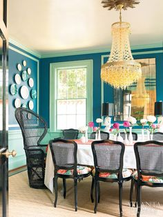 Behind black lacquer doors, the dining room bold color palette is the perfect foil for the Murano glass chandelier. The dining room chairs are upholstered in Schumacher Chiang Mai Dragon fabric. Black fanback peacock chair, mint green molding and teal paint