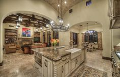 Elegant Kitchen that open up to a living room with exposed wooden beams.
