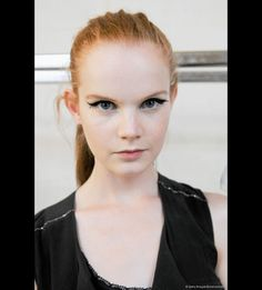 3b6ae5dd0ca6 A model backstage showed off intense eye makeup marked by bold cat-flick  eyeliner during