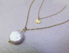 "Layered Pearl Necklace Beautiful and classy - perfect for special events or as a gift! - One genuine freshwater pearl - Chain is available in 14k gold filled or sterling silver - A delicate gold plated or a silver rhodium wavy disk adorns chain - Length is shown at 16"" & 19"". Choose your favorite lengths during checkout - Disk is 6mm. Pearl is approx 15mm (in addition to chain lengths) - Necklace closes with a 14k gold filled or sterling spring clasp Elegant and sophisticated! PACKAGING All…"