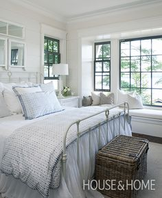 Black-framed windows bring a graphic hit to this light and airy cottage bedroom. | Photographer: Michael Graydon | Designer: Muskoka Living Interiors