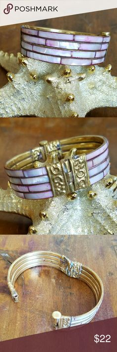 Vtg Pink Mother of Pearl Inlay Brass Bangle Vintage pink mother of pearl inlay brass bangle bracelet. Hinged and pegged brass latch and flower and scroll pattern on the brass separators.EUC. Measures 2.5in diameter x 3/4in wide. Jewelry Bracelets