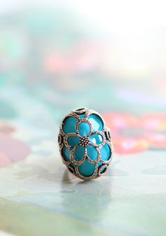 "Sea Flower Caged Ring $14.99 at shopruche.com. Elegantly designed, this ring features a sparkling aqua stone encased in the intricately designed gold hued hardware. Elasticized band.  Approx. 1.5"" wide"