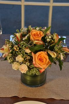 Rustic Charm Guest Table Centerpiece. This beautiful blush-hued centerpiece will delight your guests.  Filled with ivory spray roses, soft orange roses, peach alstromeria, and ivory waxflower with variegated mini pittosporum leaves.