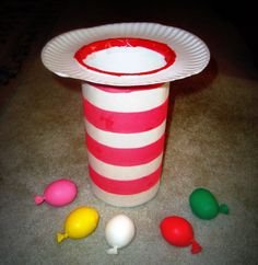 Drop or toss balloons into the striped paper hat.