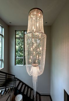We made this custom 15 foot by 39 inch chandelier for a customer's foyer. We used Swarovski elements and low voltage light glass elements. The customer later told us people often stop in front of her house to admire the chandelier.