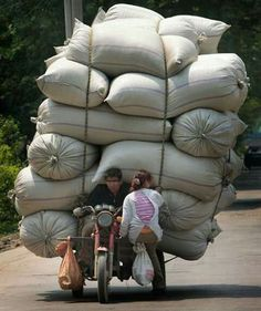A man and a woman sit on a motor tricycle carrying bags of goods in Nanjing, China. Picture: China Foto Press / Barcroft Media Reminds me of Hanoi Pancreatitis In Dogs, Scooter Bike, Nanjing, Life Is Hard, Tricycle, People Around The World, Carry On, Transportation, Funny Pictures