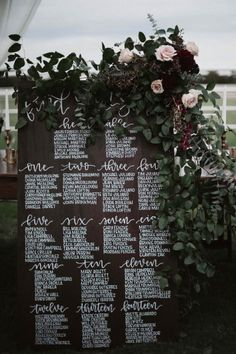 Wooden seating chart accented with greenery and soft pink flowers | Image by a sea of love