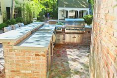 Brick patio with built-in outdoor kitchen and dining spaces. Design includes stainless steel appliances and built-in bar with cafe chairs and metal and glass outdoor dining table with folding chairs. #brick #brickpatio #outdoordining #outdoorcooking #outdoorkitchen #outdoorspace #patiodesign #patiofurniture #outdoorbar #cookingoutdoors #builtinkitchen #builtinoutdoorkitchen #builtingrill #builtinbarbecue #barbecuegrill #grilling #brickkitchen #patio #landscapearchitecture #landscapedesign