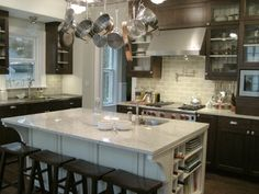 Love the hanging pots over the center island. Gives the kitchen a lived in feel.