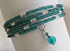 This one of a kind memory wire bracelet is made using green teal and silver seed beads. It is accented with two 6 mm green teal round glass beads. This bracelet wraps onto your wrist--it has no clasp and the memory wire will always hold its round shape. Its diameter, unstretched, is