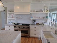 Custom Kitchen Designed by Churchville Kitchen & Home Design, White Painted Cabinetry, Wood Paneled Hood, White Carrera Marble Countertops, Stainless Steel Appliances, Wolf Range, Bin Pulls, Farm Sink, Wood Floor, Beaded Board Ceiling