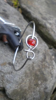 made from a stainless steel bicycle spoke...she is an amazing artist!  Bicycle Jewelry  Bicycle Spoke Bracelet by Winterwomandesigns