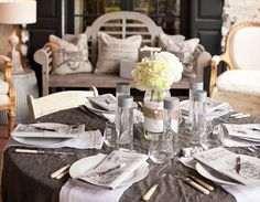 The Table Setting The sophisticated table settings included a simple hydrangea centerpiece. Instead of traditional vases, old-fashioned water bottles were wrapped in white cotton and burlap and secured with a white diaper pin.
