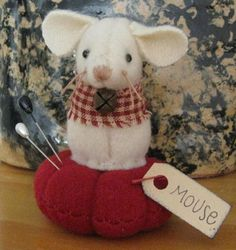 Wool Mouse on tufted wool cushion, Homespun collar with rusty jingle bell. Pins may vary