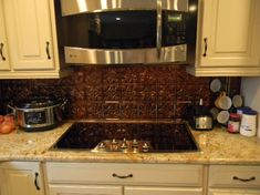 bronze fasade backsplash   The new kitchen opens up to the living room for easier entertaining.