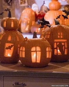 DIY Haunted Pumpkin Village - Small windows are cut out form pumpkins to give the impression of haunted dwellings. Bats and ghosts peek at us from within.