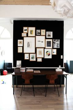 dark gallery wall, workspace in the center of the room as a divider.