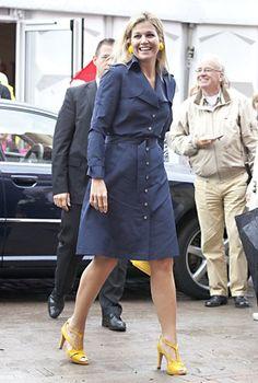 Diese dunkelblaue Mantelkleid trägt Máxima gerne und immer mit jeweils knalligen Schuhen, dazu passenden Ohrringen und Tasche, mal in Rot oder wie hier in sonnigem Gelb.