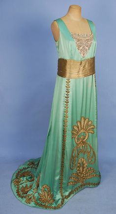 1920's aqua satin evening gown (round neck & sleeveless) with beaded net bodice inset. Wide gold lame waistband. The skirt is covered with heavy metallic embroidery, cording & applique in scroll work and feather pattern.