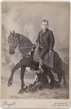 """Boy on a Studio Prop Horse - Cabinet Card. """"The Wright studio in Willamsport and Renova Pennsylvania had a prop that I have never seen in any other photograph. A boy sits on a horse made of cut out flat panels that have been elaborately painted. A flat cut-out stump added stability to the arrangement. A real saddle rests on a painted saddle blanket that looks more like a dresser scarf than a saddle blanket to me. The boy wears short pants and a double breasted suit and carries a whip."""""""