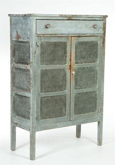 """PIE SAFE.   Midwestern, mid 19th century, poplar. One drawer over two doors, total of twelve tins punched with a """"butterfly"""" pattern. Retains old grey paint. Minor imperfections. 57 1/2""""h. 38 3/4""""w. 17 1/2""""d."""