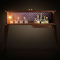 Our stunning whisky or cocktail bar is hand made in the UK from either solid American Black Walnut or Blackened Ash. The quilted back panel comes in sumptuous Grey Berry silk or rock