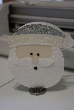 Cricut Doodlecharms - Santa Cut at 6 Pieces embossed and Glittered as Shown, Black brads for eyes, Black circle for mouth