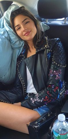 Who made Olivia Culpo's black handbag and floral leather jacket?