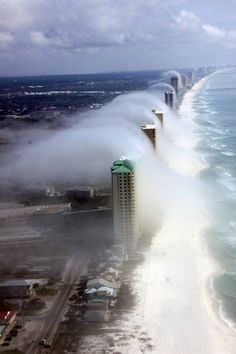 This stunning photograph taken by a helicopter pilot showed what looked like a tsunami poised to crash over the Florida coastline. But it was in fact just waves of clouds tumbling over buildings.