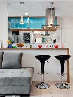 Sofá + balcão: em seu apartamento de 60 m² com cozinha integrada, o arquiteto Daniel Tesser, de São Paulo, ganhou mais espaço encostando o sofá na meia parede que isola as áreas. O tampo de madeira do balcão se prolonga, formando uma estreita prateleira acima do estofado. Ao lado, ficam as banquetas altas Classic Preta Belfix, compradas a R$ 139 cada na Loja Casa by Mobly. Pendentes de inox reforçam a atmosfera contemporânea do projeto