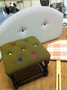 A small quirky footstool. Upholstered in a fine woven wool in moss green. Deep buttoned with wool felt balls, then hand pleated to finish. A single headboard upholstered in a navy blue ticking, with denim buttons to finish. A single headboard. Upholstered in a candy pink plaid wool blanket... Take a L@@K at KERRY COLSON UPHOLSTERY on Facebook for more unusual upholstery photos. :0)