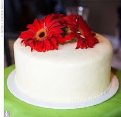 Small and simple. This one: Single layer cakes did double-duty as desserts and centerpieces for each guest table. Red gerbera daisies brought in a floral touch to the unique table toppers.