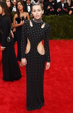 Miley Cyrus in a cut-out studded Alexander Wang dress, ear cuff, and sleek blue/gray hair at the 2015 Met Gala