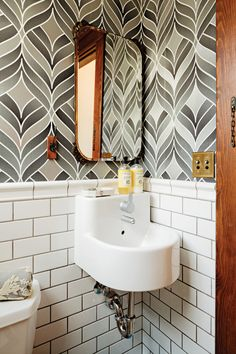 Bath mixes up old and new styles with Ikea sink, '70s-inspired wallpaper, vintage mirror, and subway tile with dark grout.