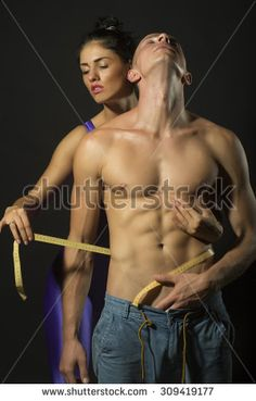 Sexy young heathy sporting couple of naked man with strong muscular body and pretty slim girl in purple supplex catsuit with yellow tape measure standing on grey studio background, vertical picture