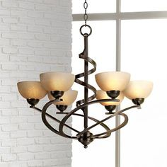 Inspired by classic iron chandeliers, this modern and transitional look features an artfully shaped swirl metal frame.