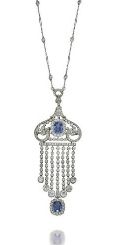 A BELLE EPOQUE SAPPHIRE AND DIAMOND PENDANT  The detachable pendant/brooch designed as a tassel of diamond collets, with a cushion-shaped sapphire terminal, to the diamond-set scrolling top centering upon a cushion-shaped sapphire, suspended from an associated fine link chain enhanced with spectacle-set diamonds, 1910s