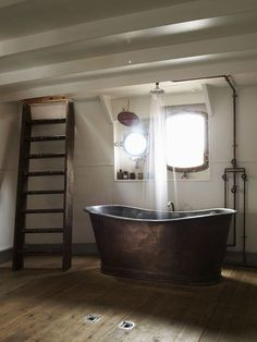 bathroom, copper curvy tub, ladder instead of stairs, nautical look, wood floors with drains, shower head center of tub..stunning