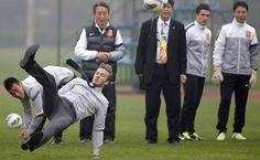 O ex-capitão da seleção inglesa, David Beckham, escorrega ao chutar bola durante visita em Wuhan, China