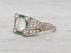 Art Decovintage engagement ring made in platinumand centered with a 1.01 caratGIA certified old European cut diamond with J color and VS1 clarity. Accented with single cut diamonds and calibre cut emeralds. Circa 1920 This piece combines the Art Deco period's most well known details. Colored gemstones, geometric angles, and delicate engraving. Diamond and gold mining has caused devastation in areassuch as Africa, wreaking havoc on delicate ecosystems and communities. Choosing to go…