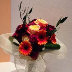 Bouquet autunnale dai colori vivaci con gerbere, rise, anemoni, garofani, ruscus e aspidistra