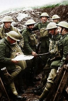 Soldiers from the Kings Liverpool Regiment listening to the news being read out as they wait in their trench during World War One. 1918.