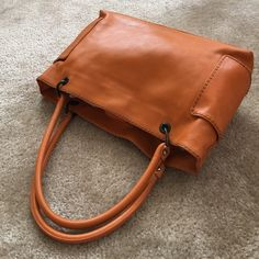 Orange leather tote, made in Italy Orange leather tote in lovely preowned gently worn condition. Made in Italy by Plinio Visona. Has three large interior pockets with additional zipper compartments.  Two side pockets and snap closure. Minor wear on the bottom corners.  Please ask any questions you may have before purchasing. 🚫Trades, 🚫Low ball offers please. Bags Totes