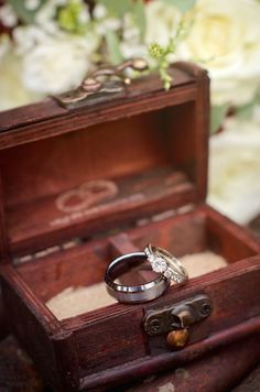 """Wedding rings in a small chest. """"And the two become one"""" is inscribed on the lid."""
