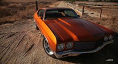 A beautiful 1970 Chevelle thats burnt orange in color on a desolate dirt road!