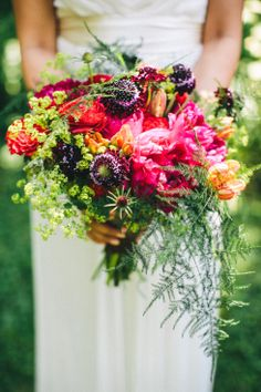 bright pink, purple, red and orange wedding bouquet with peonies, scabiosa, ferns an assortment of other beautiful flowers | photo: photo: www.ericlundgren.net | floral design: camrose hill